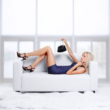 Blond meisje op bank Stock Foto's