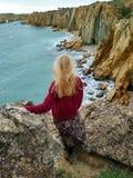 Blond meisje op de klippen stock foto