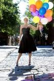 Blond met ballons uit in de zon Stock Afbeelding