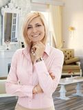 Blond mid-adult woman in elegant living room stock photography