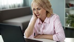 Blond middle-aged woman feeling bored watching online video, falling asleep. Stock photo royalty free stock image