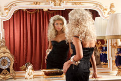 Blond and mirror. Portrait of a pretty blond admiring herself in the mirror Royalty Free Stock Images