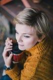 Blond mit den blauen Augen, die nahe See mit Schale heißem Tee sitzen Lizenzfreie Stockbilder