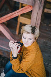 Blond mit den blauen Augen, die nahe See mit Schale heißem Tee sitzen Stockbild