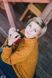 Blond mit den blauen Augen, die nahe See mit Schale heißem Tee sitzen Stockfotos