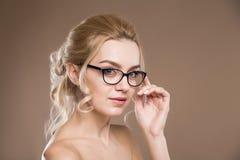 Blond mit der Hand nahe Gläsern Stockfotografie