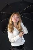 Blond mit einem schwarzen Regenschirm Lizenzfreie Stockfotografie