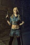 Blond mit Klinge und Gewehr Stockfotografie