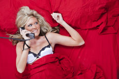 Blond Model in Bed on Phone Stock Photo
