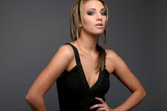 Blond model in black dress. Beautiful blond model in black dress posing on grey background Stock Images