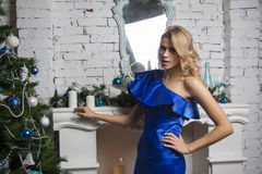 Blond model in blue silk dress near new year tree Royalty Free Stock Photography