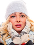 Blond model with hands to face. A attractive blond model is wearing winter clothes looking straight into the camera with both hands up to her face stock image