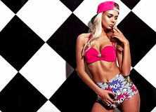 Blond model in rnb style clothes with pink colorful baseball cap. Posing near chess wall Stock Photos