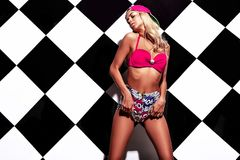 Blond model in rnb style clothes with pink colorful baseball cap