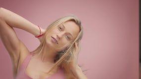 Blond model in studio op roze achtergrond met haar die in lucht blazen stock footage