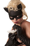 Blond model wearing black cat, drinking milk. Portrait of the blond model wearing black cat, licking - drinking milk from the martini glass royalty free stock images