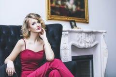 Blond modell för härlig kvinna i en röd jumpsuit en innegrej och fotografering för bildbyråer