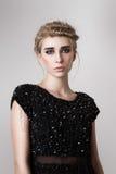 Blond modell för mode med den svarta klänningen arkivfoton