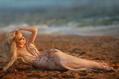 Blond modell för ung kvinna med ljus makeup utomhus i modestil i aftonklänning bak blå himmel Royaltyfri Fotografi