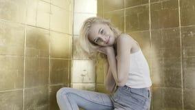 Blond modell med lockigt hår som framme sitter av den guld- tegelstenväggen och vippar på hennes huvud actinium h?rligt flickabar lager videofilmer