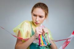 Blond modell som rymmer den lilla plastpåsen med rakknivar inom arkivbild