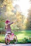 Blond modieus langharig aantrekkelijk meisje in korte kleding met damefiets in zonnig park stock foto