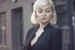 Blond mooi model in portret van de zonsondergang het lichte in openlucht close-up in zwart kostuum en met oortunnels geen make-up stock foto