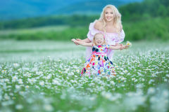 Blond mother with cute little daughter wearing white colourful pink dresses in chamomile field, summer time Enjoying spending time. Together happy childhood stock image