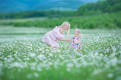 Blond mother with cute little daughter wearing white colourful pink dresses in chamomile field, summer time Enjoying spending time. Together happy childhood royalty free stock photography