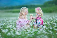 Blond mother with cute little daughter wearing white colourful pink dresses in chamomile field, summer time Enjoying spending time royalty free stock images