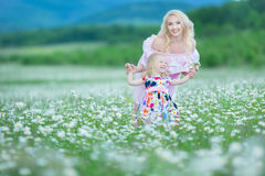 Blond mother with cute little daughter wearing white colourful pink dresses in chamomile field, summer time Enjoying spending time stock image