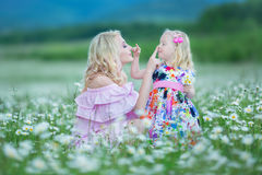 Blond mother with cute little daughter wearing white colourful pink dresses in chamomile field, summer time Enjoying spending time stock photography