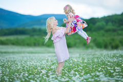 Blond mother with cute little daughter wearing white colourful pink dresses in chamomile field, summer time Enjoying spending time royalty free stock photo