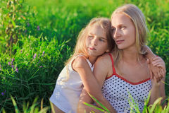 Blond mother and daughter sitting on green grass Royalty Free Stock Photos