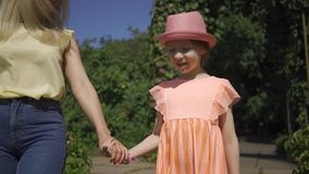 Cute blond mother walking with small adorable daughter in the summer garden holding hands. Happy family. Woman and girl stock footage