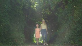 Blond mother walking with daughter in the summer garden or park holding hands. Happy family. Connection with nature stock video