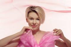 Blond naken kvinna i stor rosa färgpilbåge Royaltyfri Fotografi
