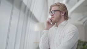 Blond nervous man in glasses standing in a light comfortable office talking by cellphone. Handsome businessman involved. Blond nervous man in glasses standing in stock video