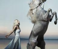 Blond nymf som poserar med den majestätiska hästen Royaltyfria Foton