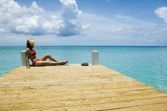 Blond on pier. A sexy blond woman relaxes in the caribbean sun at the end of a dock Royalty Free Stock Photos