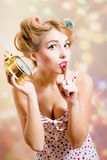 Blond pinup green-eyed woman with curlers holding Royalty Free Stock Images