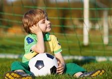 Blond pojke av spela fotboll 4 med fotboll på fotbollfält Fotografering för Bildbyråer