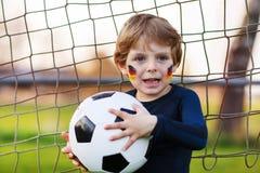 Blond pojke av spela fotboll 4 med fotboll på fotbollfält Arkivfoto