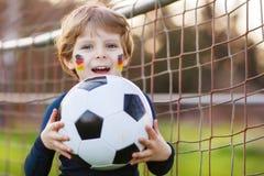 Blond pojke av spela fotboll 4 med fotboll på fotbollfält Royaltyfri Fotografi