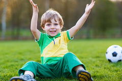 Blond pojke av spela fotboll 4 med fotboll på fotbollfält Arkivfoton