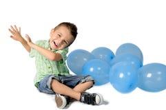 Blond pojke med ballonger på vit bakgrund fotografering för bildbyråer