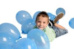 Blond pojke med ballonger på vit bakgrund Arkivfoto