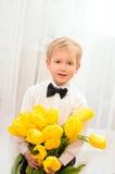 Blond pojke med buketten av gula blommor royaltyfri fotografi