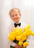 Blond pojke med buketten av gula blommor royaltyfria bilder