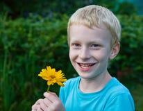 Blond pojke med en blomma Arkivfoton